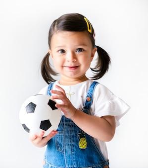 Szczęśliwa mała dziewczynka trzyma futbol