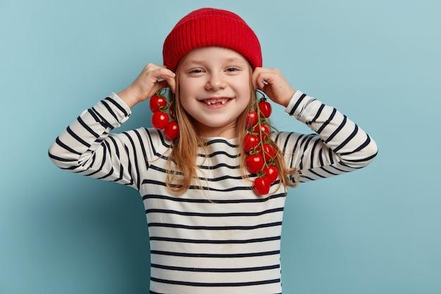 Szczęśliwa mała dziewczynka trzyma pomidory czereśniowe
