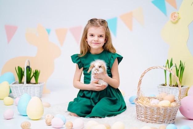 Szczęśliwa mała dziewczynka trzyma ślicznego puszystego królika blisko malujących wielkanocnych jajek