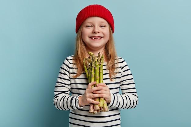 Szczęśliwa mała dziewczynka trzyma szparagi