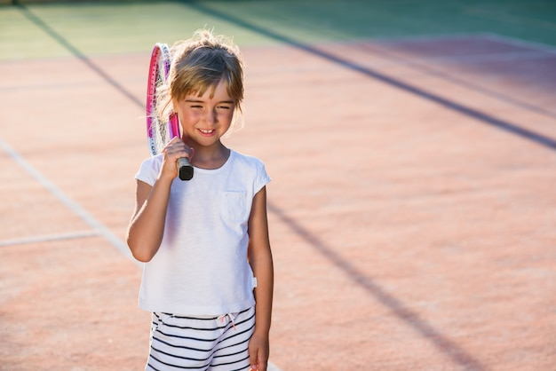 Szczęśliwa mała dziewczynka ubierał bielu mundur z tenisowym kantem na ramieniu na tle plenerowy tenisowy kort przy zmierzchem.