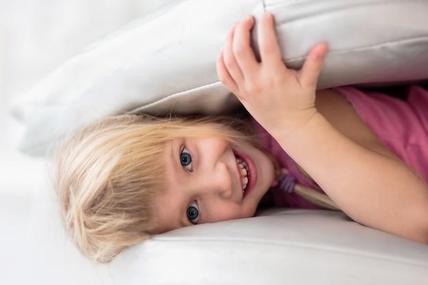 Szczęśliwa mała dziewczynka uśmiecha się podczas zabawy poduszkami w łóżku