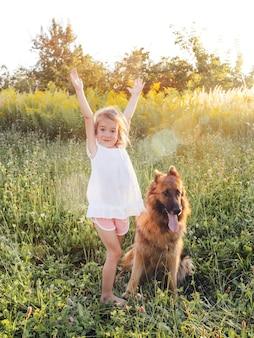 Szczęśliwa mała dziewczynka w białej sukni stoi obok dużego psa z rękami do góry na zielonej trawie. owczarek niemiecki.