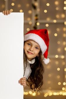 Szczęśliwa mała dziewczynka w czerwonym santa hat trzyma biały karton pusty transparent z pustą przestrzenią