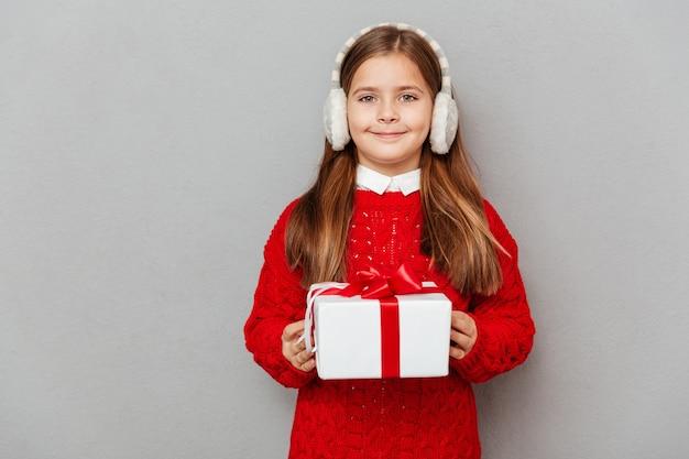 Szczęśliwa mała dziewczynka w czerwonym swetrze i nausznikach z prezentem