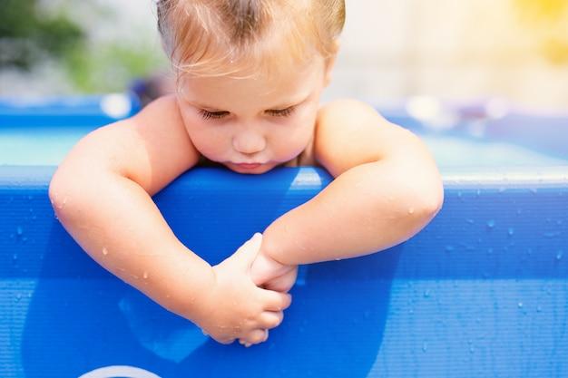 Szczęśliwa mała dziewczynka w czerwonym swimsuit doskakiwaniu w plenerowego pływackiego basen w domu. dziewczynka uczy się pływać. wodna zabawa dla dzieci.