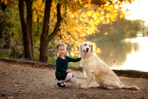 Szczęśliwa mała dziewczynka w parku w jesieni z psem