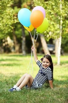 Szczęśliwa mała dziewczynka w pasiastej sukience z kolorowymi balonami w parku