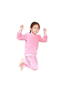 Szczęśliwa mała dziewczynka w różowym dresu doskakiwaniu na powietrzu