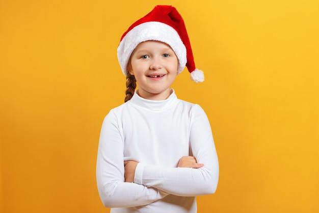 Szczęśliwa mała dziewczynka w santa kapeluszu.