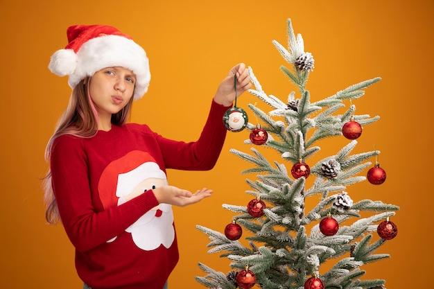 Szczęśliwa mała dziewczynka w świątecznym swetrze i mikołajowym kapeluszu wiszą kulki na choince prezentując ręką oh jej rękę wyglądającą pewnie na pomarańczowym tle