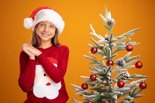 Szczęśliwa mała dziewczynka w świątecznym swetrze i santa hat trzymając się za ręce razem uśmiechając się czekając na niespodziankę stojącą obok choinki na pomarańczowym tle