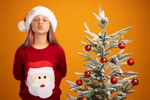 Szczęśliwa mała dziewczynka w świątecznym swetrze i santa hat trzymając usta jak całowanie stojąc obok choinki na pomarańczowym tle