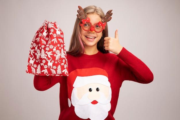 Szczęśliwa mała dziewczynka w świątecznym swetrze w zabawnych okularach imprezowych trzymając santa czerwoną torbę z prezentami, patrząc na kamery, uśmiechając się radośnie pokazując kciuk do góry stojący na białym tle