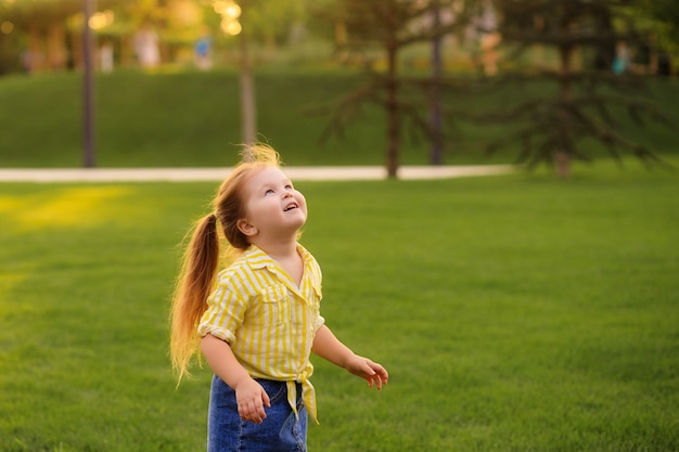 Szczęśliwa mała dziewczynka w wieku 4-5 lat bawi się latem w parku z baniek mydlanych. styl życia dzieci.