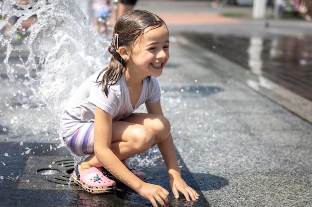 Szczęśliwa mała dziewczynka wśród rozprysków wody miejskiej fontanny.