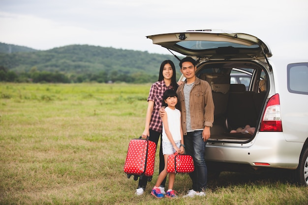 Szczęśliwa mała dziewczynka z azjatykcim rodzinnym obsiadaniem w samochodzie