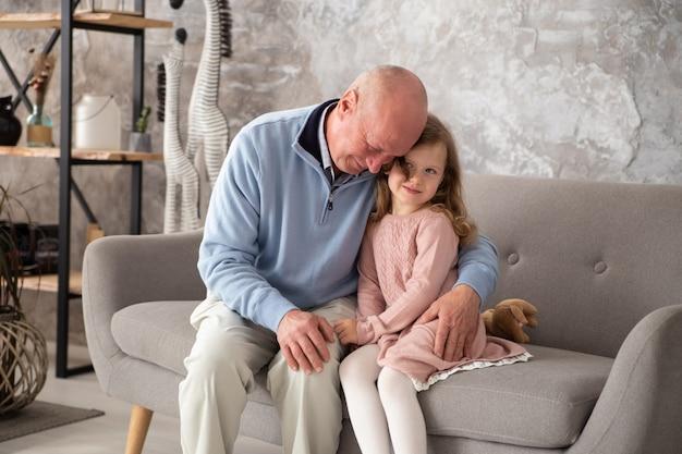 Szczęśliwa mała dziewczynka z dziadkiem bawić się w domu. rodzina spędza czas w domu
