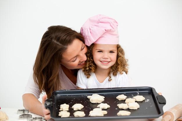 Szczęśliwa mała dziewczynka z jej matką pokazuje talerza z ciastkami