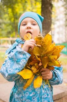 Szczęśliwa mała dziewczynka z jesień liśćmi w parku