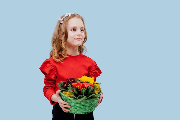 Szczęśliwa mała dziewczynka z koszem kwiatów w ręku ubrana na czerwono, odizolowana na niebiesko