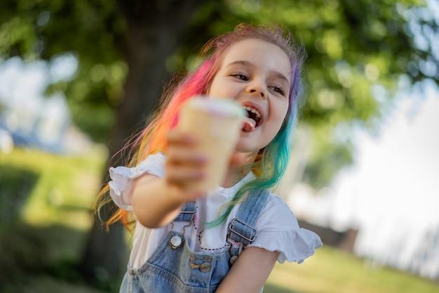Szczęśliwa mała dziewczynka z lodami na zewnątrz. obraz z selektywnym skupieniem
