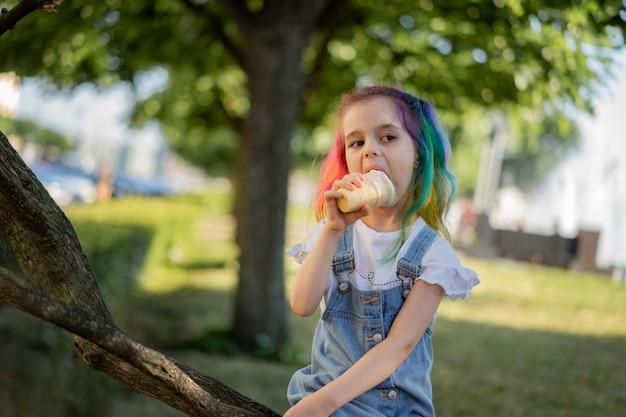 Szczęśliwa mała dziewczynka z lodami na zewnątrz obrazu z selektywną ostrością