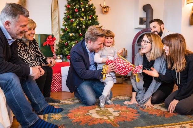 Szczęśliwa mała dziewczynka z rodzinnym unboxing prezentem na święto bożęgo narodzenia