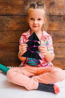 Szczęśliwa mała dziewczynka z świątecznym wystrojem jodły