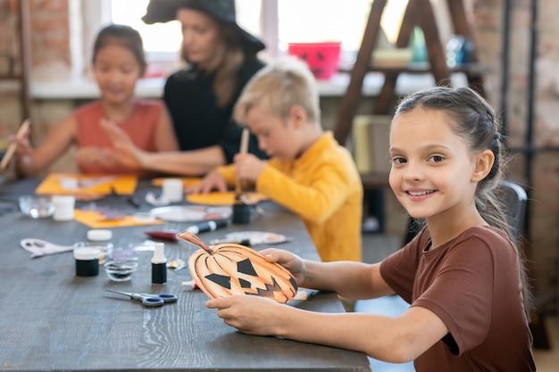 Szczęśliwa mała dziewczynka z symbolem halloween siedząca przy stole