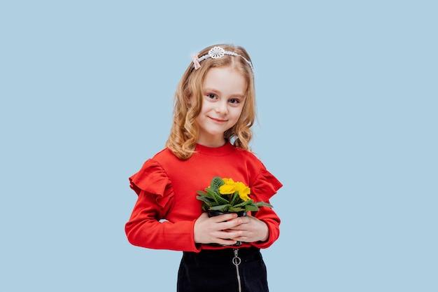Szczęśliwa mała dziewczynka z wiosennym kwiatem w dłoni, ubrana na czerwono, odizolowana na niebiesko