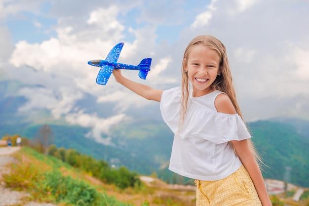 Szczęśliwa mała dziewczynka z zabawkarskim samolotem w rękach w górach