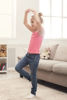 Szczęśliwa mała dziewczynka zabawy w domu. dorywczo uśmiechnięte dziecko tańczy i śpiewa w pokoju pełnym światła słonecznego. rozrywka i rozrywka dla dzieci, kopia przestrzeń
