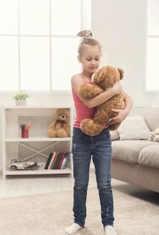 Szczęśliwa mała dziewczynka zabawy w domu. dorywczo uśmiechnięte dziecko tańczy z misiem i śpiewa w pokoju. rozrywka i rozrywka dla dzieci, kopia przestrzeń