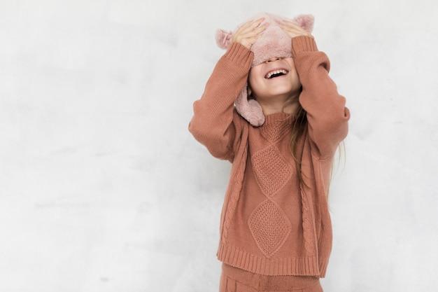 Szczęśliwa mała dziewczynka zakrywa jej twarz