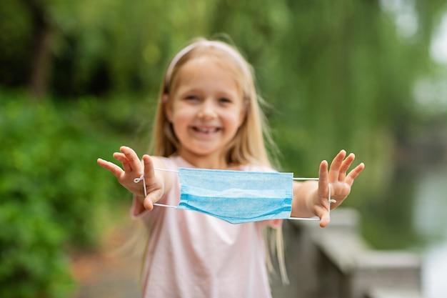 Szczęśliwa mała dziewczynka zdejmuje ochronną medyczną maskę