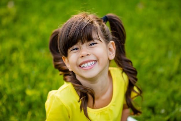 Szczęśliwa mała indyjska dziewczyna w żółtej koszulce śmieje się latem na trawniku