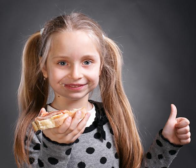 Szczęśliwa mała kobieta je chleb i masło z rybami i pokazuje tak znak