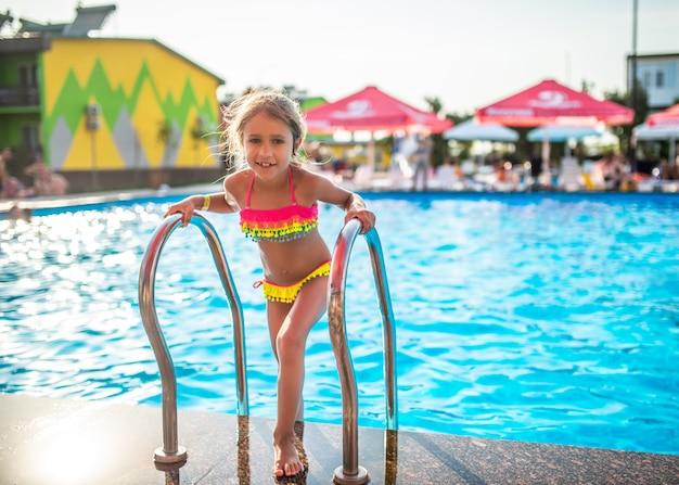 Szczęśliwa mała ładna dziewczyna w kolorowym kostiumu kąpielowym