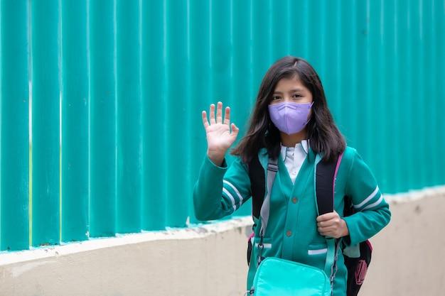 Szczęśliwa mała meksykańska dziewczynka nosząca maskę na plecach do szkoły