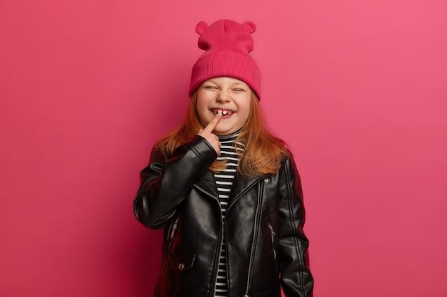 Szczęśliwa mała rudowłosa dziewczynka w modnych ubraniach, wskazuje na swój nowy ząb, ma niezapomniane dzieciństwo, z przyjemnością mruży twarz, pozuje na różowej ścianie. koncepcja wzrostu dzieci