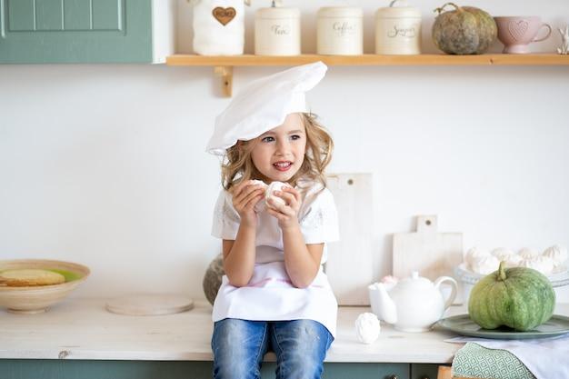 Szczęśliwa mała szef kuchni dziewczyna bawić się w kuchni w domu