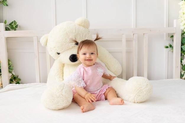 Szczęśliwa mała sześciomiesięczna dziewczynka siedzi na białym łóżku w różowych ubraniach, z wielkim misiem i uśmiechnięta