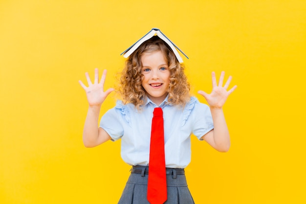 Szczęśliwa mała uczennica z książką na głowie, stojąc na żółtym tle. powrót do koncepcji szkoły