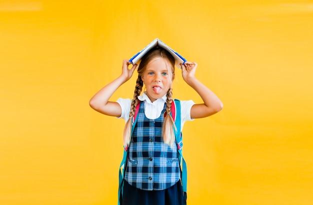 Szczęśliwa mała uczennica z książką na głowie, stojąc na żółtym tle.