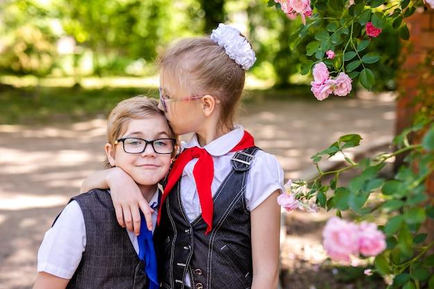 Szczęśliwa mała uczennica z szkłami i czerwonym krawatem. powrót do szkoły na zewnątrz.