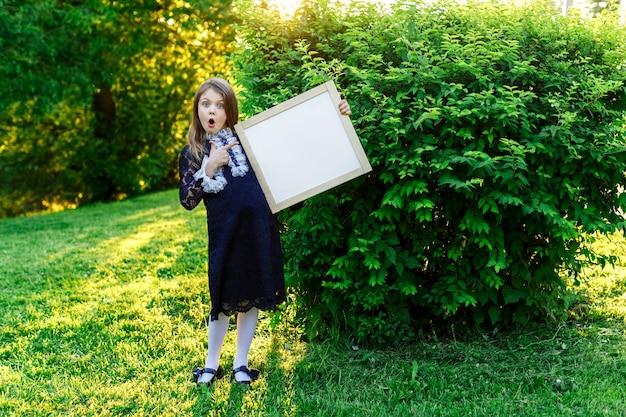 Szczęśliwa mała uczennica ze zdziwieniem wskazuje miejsce na tekst reklamy letniej szkoły z miejscem na tekst