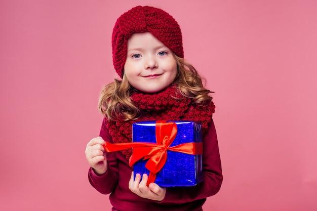 Szczęśliwa mała uśmiechnięta blondynka kręcone fryzury dziewczyna w dzianym czerwonym kapeluszu z świątecznym pudełkiem z kokardą na różowym tle studio. noworoczny prezent w rękach dziecka płci żeńskiej, która ma życzenie copyspace