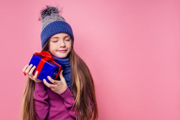Szczęśliwa mała uśmiechnięta blondynka kręcone fryzury dziewczyna w dzianym niebiesko-szarym kapeluszu i szaliku z świątecznym pudełkiem na różowym tle studio. nowy rok obecny w rękach dziecka płci żeńskiej co życzenie copyspace.