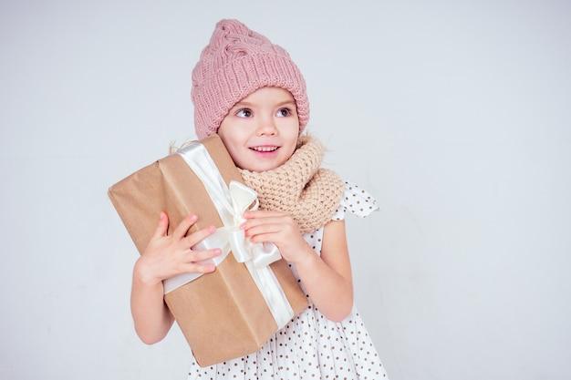 Szczęśliwa mała uśmiechnięta blondynka kręcone fryzury dziewczyna w dzianym różowym kapeluszu z świątecznym pudełkiem z kokardą na białym tle studio. nowy rok obecny w rękach dziecka płci żeńskiej co życzenie copyspace.